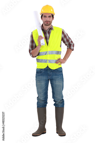 Engineer in a reflective vest with plans
