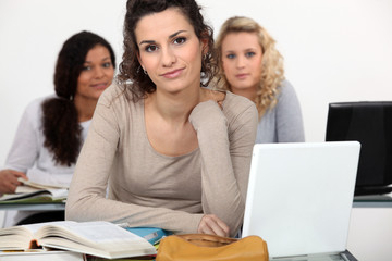 Three female students studying with their laptops.
