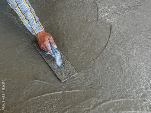 hand using trowel to finish wet concrete floor