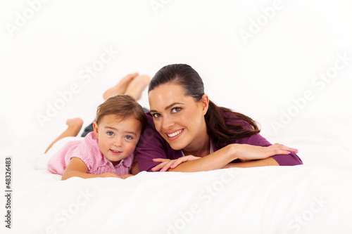happy mother and baby girl lying on bed