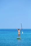 Aspirational beach lifestyle woman on paddleboard poster
