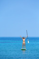 Aspirational beach lifestyle woman on paddleboard