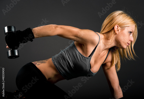 Fit woman exercising with weights over a dark background