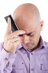 Worried bald  man with cellphone