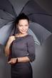 portrait of beautiful fashionable woman with umbrella on dark ba