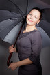 portrait of beautiful fashionable woman with umbrella on dark ba