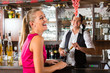 Woman ordering glass of wine at bar