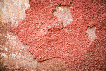 Red plaster partially peeling off of a wall