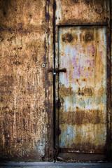 Rusty old brown metal door with a lock