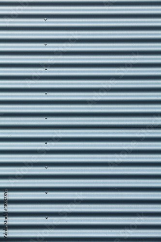 Tall shot of blue corrugated metal with bolts