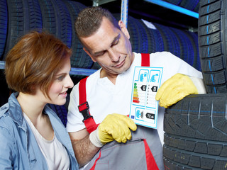 Motor mechanic explains to a customer tire labeling in a garage