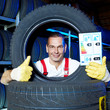 Motor mechanic shows thumb up for tire label in a garage