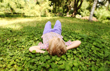 Little boy rest on the green park meadow