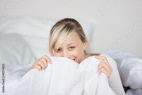 lachende frau versteckt sich hinter bettdecke