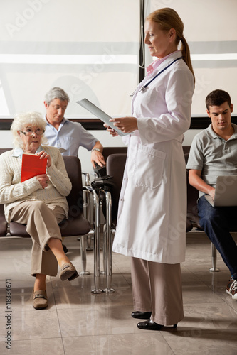 Doctor Reading File With People In Lobby