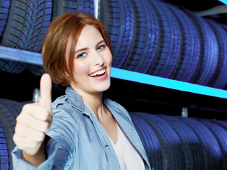 Female customer in garage shows thumb up for good service
