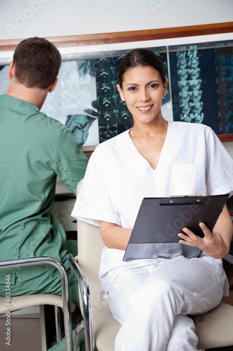 Female Medical Technician Holding Clipboard