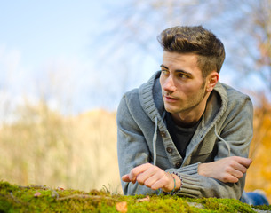 Attractive young man outdoors in nature lying on moss