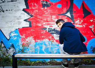 Young man with hoodie sitting on bench in front of graffiti