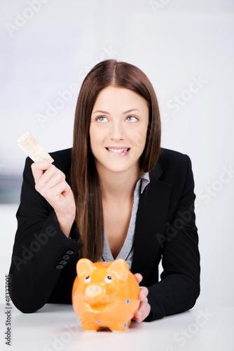 lächelnde frau hält hand über sparschwein