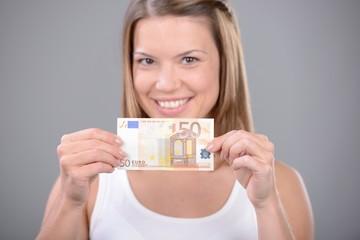 lächelnde frau zeigt 50 euro schein