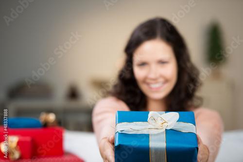 lächelnde frau überreicht ein weihnachtsgeschenk