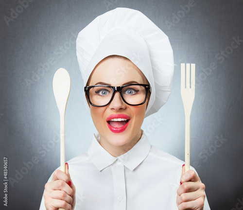 Portrait of laughing woman cook chef holding fork and spoon