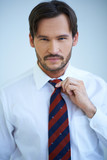 Attractive man adjusting his tie