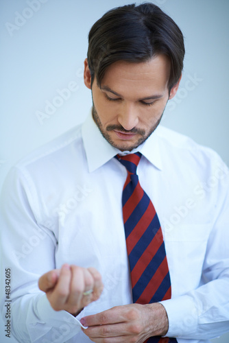 Attractive young man doing up his shirt cuffs