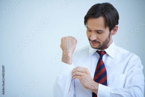 Young man buttoning his cuffs