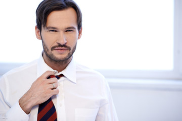 Attractive man adjusting the knot of his tie