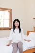 ベッドに腰掛ける若い女性