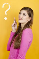 Junge Frau deutet nach oben auf ein Fragezeichen