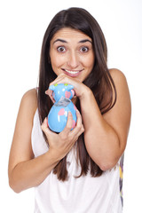 beautiful young woman smiling with a cow piggy bank
