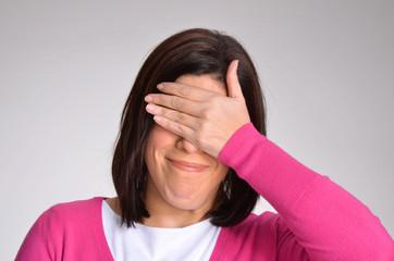 Mujer  arrepentida equivocada cubriendo sus ojos.
