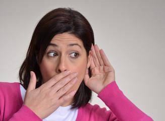 Mujer curiosa escuchando,tocando su oído,expresiva,asombrada.