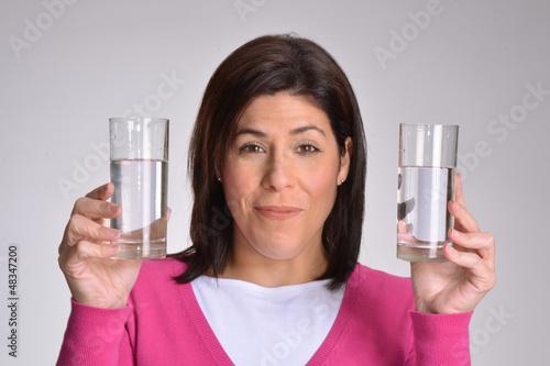 Mujer en dieta sujetando dos vasos de agua.