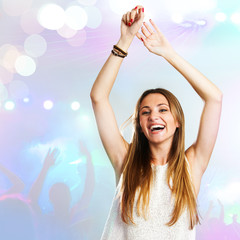 Young woman dancing with party background.