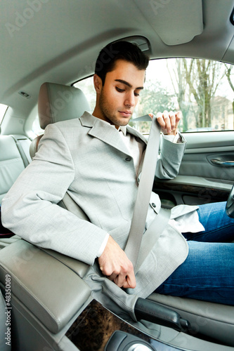 Young man fastening seat belt