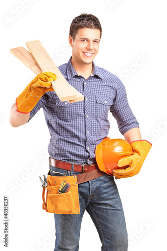 A smiling carpenter holding a helmet and sills