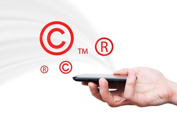 Copyright, trademark symbols flying from smartphone