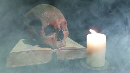 Human skull and book in the smoke