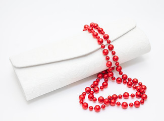Red pearl necklace with purse on white background