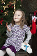 waiting for Santa Claus. Happy little girl near Christmas tree