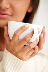 White cup in beautiful woman hands