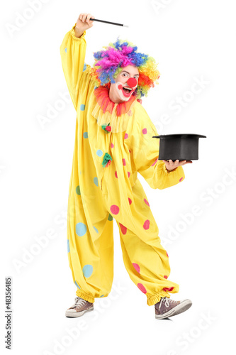 Full length portrait of a circus clown performing a magic trick