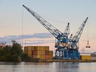 Two cranes are waiting for cargo in a dutch harbour