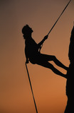 Female rock climber rapelling off a cliff