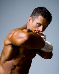 Close-up portrait of a kick-boxer in a fighting stance.