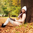 Pretty student girl with laptop in autumn park. Young European